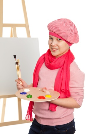 Cheerful little girl standing at the easel  Young artist holds in his hands the palette with paints