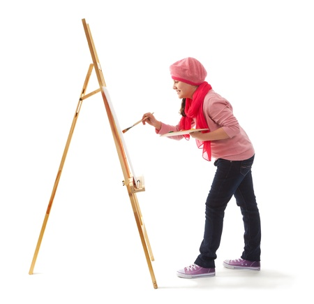 Cheerful little girl standing at the easel  Young artist holds in his hands the palette with paints  She paints   Stock Photo