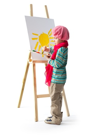 Cheerful little boy standing at the easel. Young artist holds in his hands the palette with paints. He paints the sun.  photo