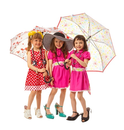 Three girls - fashion-mongers with parasols in adult shoes on white background