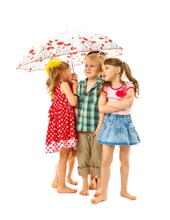Barefoot children are standing under an umbrella on a white background. They hide from summer rain. They are fun. photo