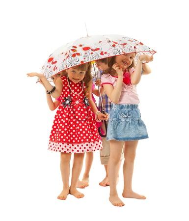 sotto la pioggia: Bambini a piedi nudi sono in piedi sotto un ombrello su uno sfondo bianco. Si nascondono da pioggia estiva. Sono divertenti.