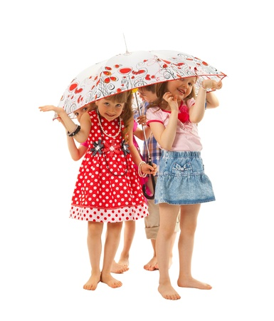 Barefoot children are standing under an umbrella on a white background. They hide from summer rain. They are fun.