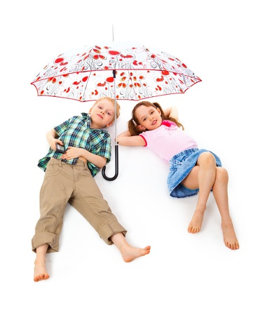 Boy and girl relaxing under an umbrella on a hot day.