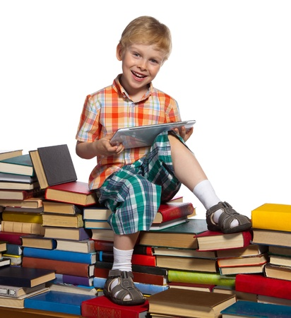 Little boy on a pile of books holds a tablet computer in his hands. photo