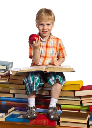 able to learn: Little boy is reading interesting book. He is setting on high stacks of books. He holds apple in his hand.