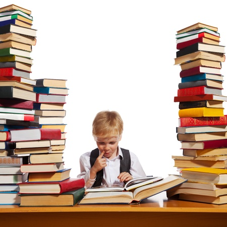 able to learn: Little boy is reading interesting book. High stacks of books are on the table near him. Stock Photo