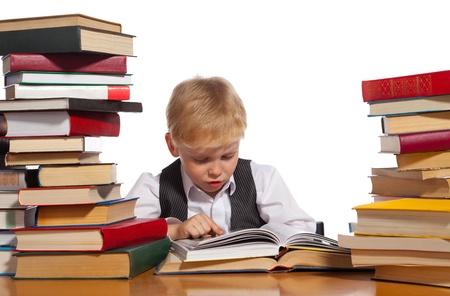 Jongetje leest interessant boek. Hoge stapels boeken zijn op de tafel naast hem. Stockfoto