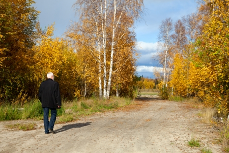 Elderly man with gray beard for a walk in the forest at the beginning autumn