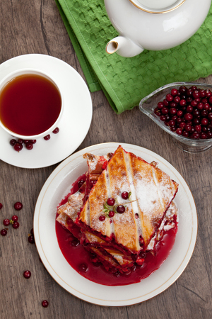 Cranberry Pie for Christmas and tasty tea with foxberry leafs are on wooden table  photo