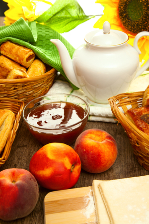 soumis: Tartes appétissants d'pâte feuilletée sont sur la table en bois, accompagnée d'une fruits frais, de la confiture de pêches et savoureux thé pour le petit déjeuner