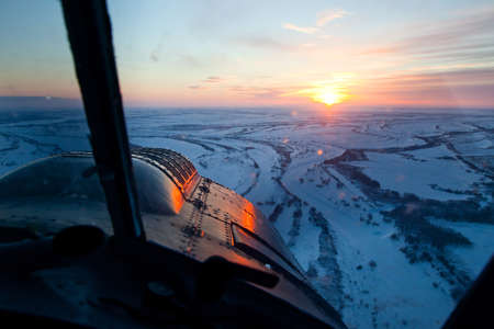 It is aerial view of the snow-covered plain at the winter sunset from the cockpit of old airplane   photo