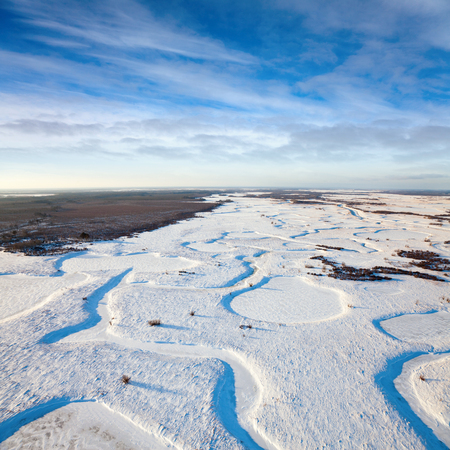 overhand: Aerial view over snowy fields with creek which fancifully winds between snowdrift