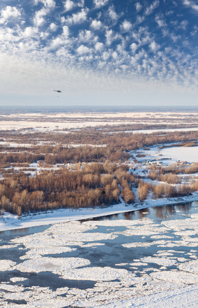drifting ice: Helicopter is flying over snow covered plain beside the large river during spring break up. Helicopter MI-8 with external load. Aerial view. Stock Photo