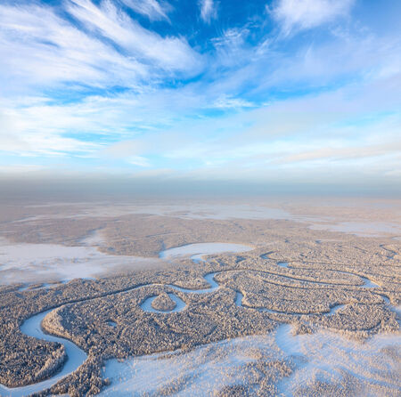 overhand: Aerial view of forest river during frozen winter day. Magnificent hoarfrost on trees.  A winter forest on rising in a hard frost. Stock Photo