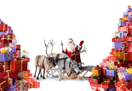 Kerstman met rendieren staan naast de enorme hoeveelheid geschenken, die hij gaat geven voor u tijdens de kerst, geïsoleerd op witte achtergrond Stockfoto