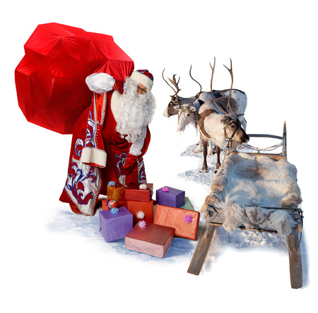 Santa Claus carries the big bag of gifts to his reindeer sleigh to give their all people during Christmas. Isolated on white background.