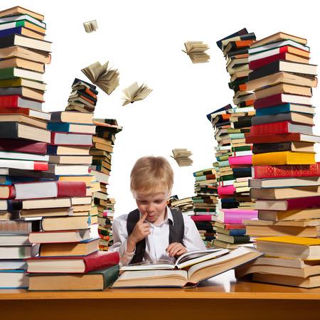 Jongetje leest interessant boek. Hoge stapels boeken zijn op de tafel in de buurt van hem.