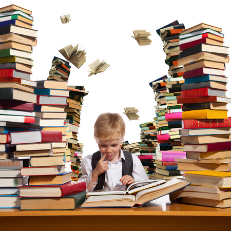 Little boy is reading interesting book. High stacks of books are on the table near him. Stock Photo