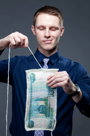 depreciation: Young businessman unweaves knit fabric that looks like a banknote. This picture symbolizes the depreciation of the currency, or depreciation of the ruble, or ruble devaluation, ruble weakening, or speculation on the currency exchange