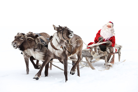 Santa Claus rides in a reindeer sleigh. He hastens to give gifts before Christmas. Reklamní fotografie - 34845728