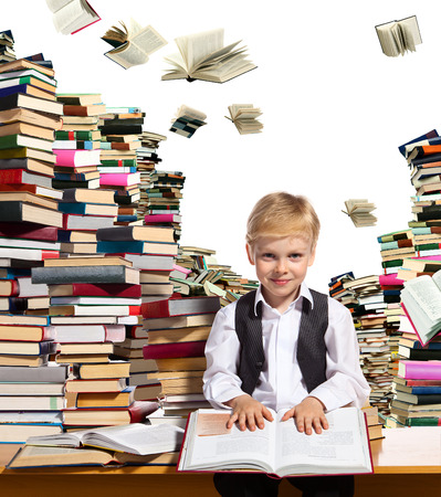 prodigy: Little boy is reading interesting book. High stacks of books are on the table near him. Stock Photo
