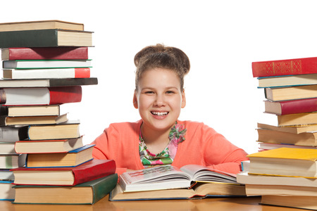 able to learn: School girl is reading interesting book. High stacks of books are on the table near her.