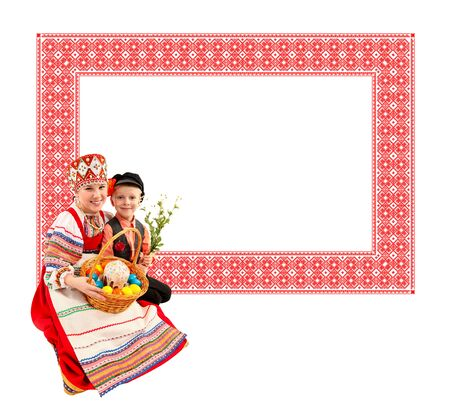 russian easter: Cheerful girl and boy dressed in traditional dress. She holds the basket with Easter eggs and a holiday cake. On russian pattern background. Stock Photo