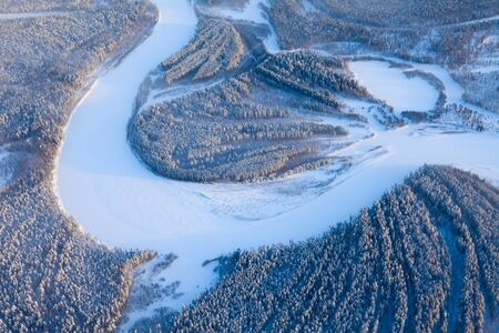 duskiness: Aerial view of forest river in time of winter day.
