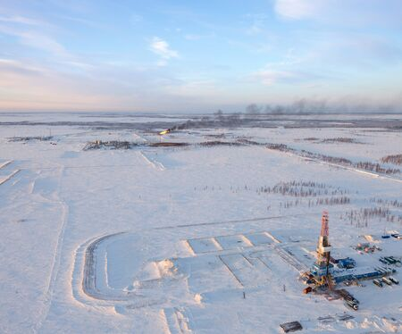 drilling: Aerial view of oil rig at an oil field in Western Siberia in the winter day. Gas-jet for gas flaring is located near the rig.
