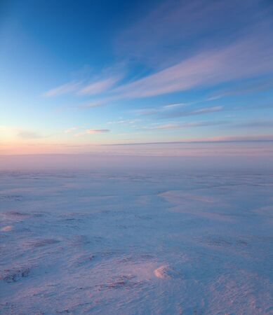 Aerial view above the endless snow covered tundra in time of short winter day. Small hill illuminated the low sun. photo