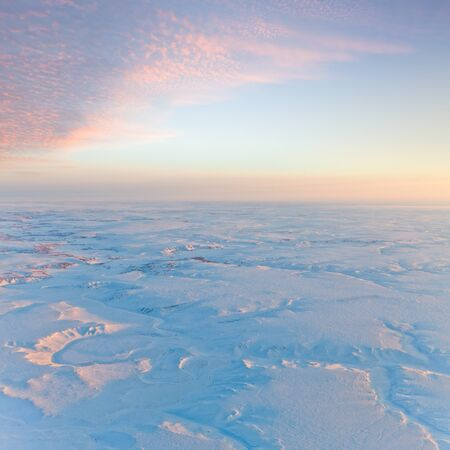 duskiness: Aerial view above the endless snow covered tundra in time of short winter day. Small hill illuminated the low sun. Stock Photo
