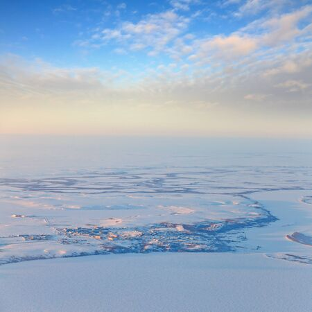 duskiness: Aerial view above the endless snow covered tundra river in time of short winter day. Small village for workers gas industry are located on the river bank.