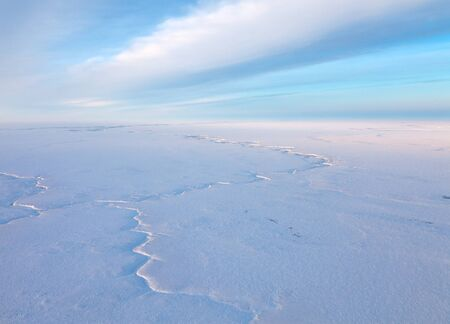 duskiness: Aerial view above the endless snow covered tundra in time of short winter day.