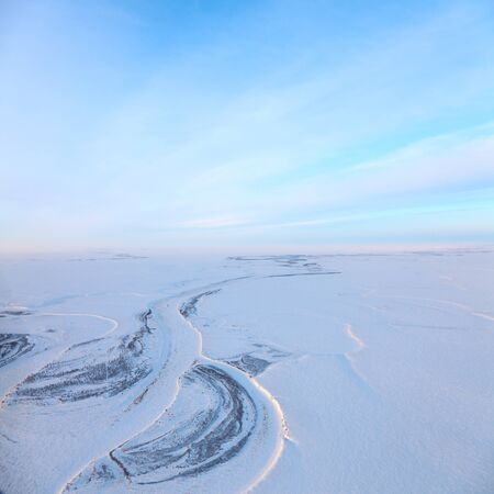 duskiness: Aerial view above the endless snow covered tundra river in time of short winter day.