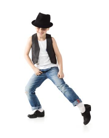 taniec: Mały chłopiec w kapeluszu i jeance tańczy na białym