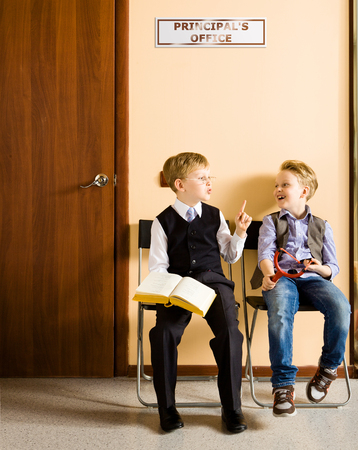 studious: Two schoolboys are sitting next to principals office. They are twin, but they have different each other behavior and clothes. For creating this picture were used two image of one and the same boy. Stock Photo