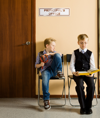 model release: Two schoolboys are sitting next to principals office. They are twin, but they have different each other behavior and clothes. One model release, because for creating this picture were used two image of one and the same boy.