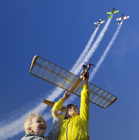 fly: Children try to run a model glider. In the same time three sport aircraft are climbing in the blue sky straight above them.
