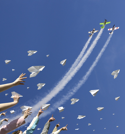 paper airplane: Children hands throw upward a lot of messages in the manner of paper airplanes. In the same time three sport aircraft are climbing in the blue sky straight above them.
