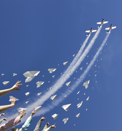 The hands of children throw upwards messages in the manner of paper airplanes.  In the same time three sport aircraft are climbing in the blue sky straight above them. 写真素材