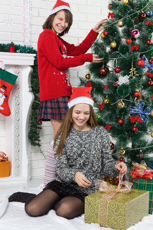 dinner jacket: Happy sisters standing near the fireplace and a Christmas tree. children waiting for the new year