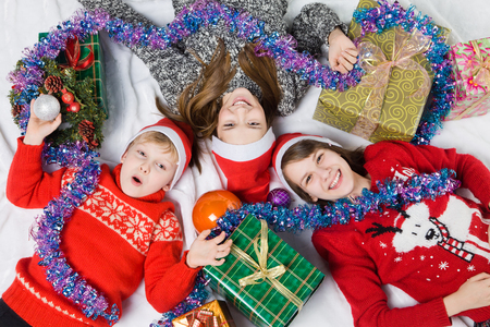 dinner jacket: Happy brother and sisters are lying on the floor with Christmas gifts during waiting for the new year