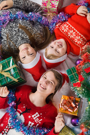 new baby: Happy brother and sisters is near a Christmas tree. children waiting for the new year Stock Photo