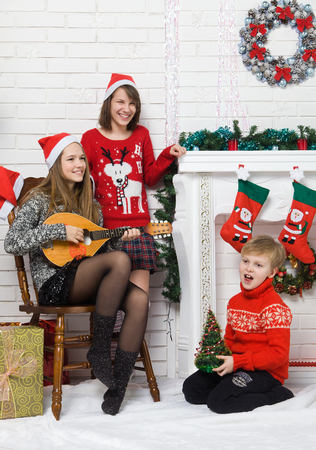 christmas funny: Happy brother and sisters are singing holiday songs near the fireplace with Christmas decoration. Children waiting for the new year