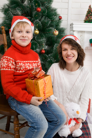 dinner jacket: Happy brother and sister standing near the fireplace and a Christmas tree. children waiting for the new year