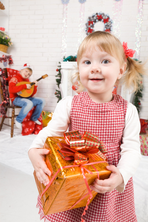 baby near christmas tree: Happy baby girl with gifts are near the fireplace and a Christmas tree during waiting for the new year. Boy plays on a domra and sings holiday songs.