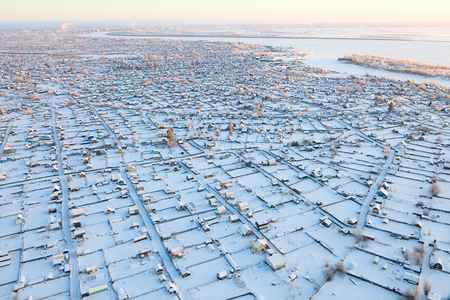aerial view over snowy suburb beside northren town Stock Photo