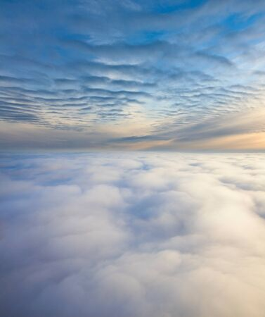 overhand: Aerial view of a cloudy sunset while flying above the clouds.