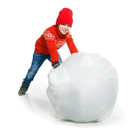 snowball: Little boy playing in the snow, isolated on white background. Children in winter. Happy kid making a big snowball for snowman Stock Photo